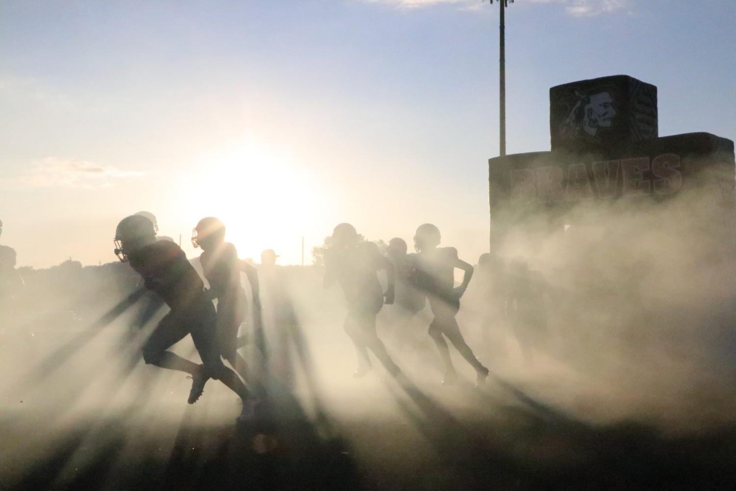 In the midst of the fog, the braves charge onto the field in the home opener on Sept. 13.